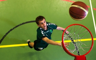 A student in the gym at Holy Cross shooting a basket ball