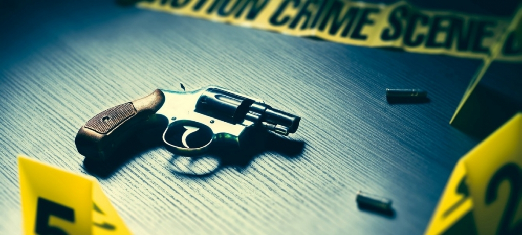 A gun, bullets and yellow crime scene tape
