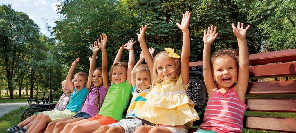 Young children sitting excitedly on a bench with their arms in the air used to illustrate the A Level English Language Course