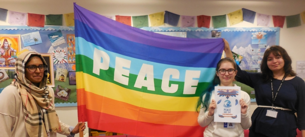 Holy Cross students holding a rainbow coloured flag that says 'Peace'