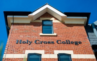 Sign reading 'Holy Cross College' on the outside of the building
